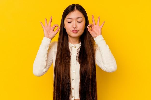 黄色で隔離された若い中国人女性は、ハードワークの一日の後にリラックスし、彼女はヨガを行っています。