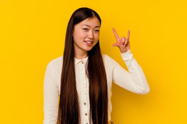 혁명 개념으로 뿔 제스처를 보여주는 노란색에 고립 된 젊은 중국 여자.