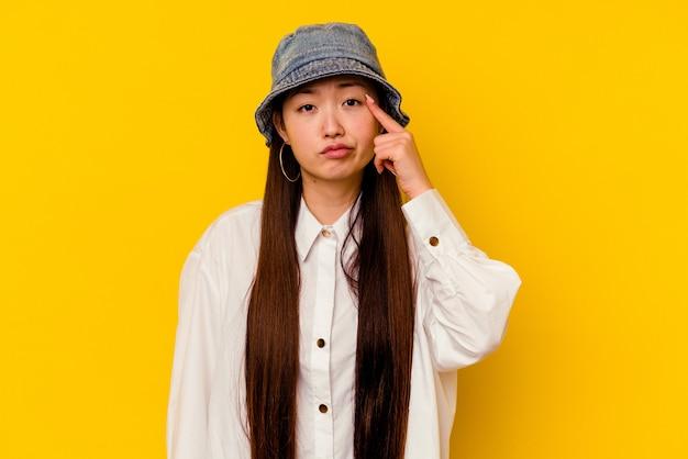 何かに不満を持って泣いて、黄色の壁に孤立した若い中国人女性