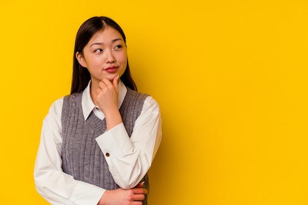 Молодая китаянка изолирована на желтой стене, глядя в сторону с сомнительным и скептическим выражением лица.