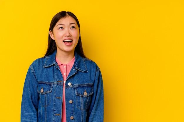 非常に怒って叫んで黄色の壁に孤立した若い中国人女性