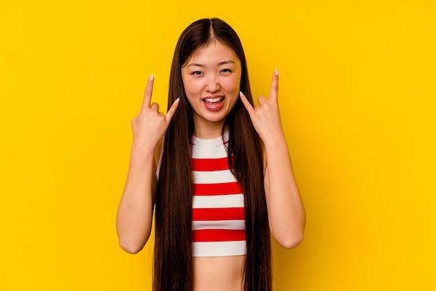 혁명 개념으로 뿔 제스처를 보여주는 노란색 벽에 고립 된 젊은 중국 여자.
