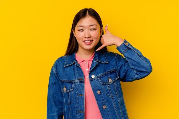 指で携帯電話の呼び出しジェスチャーを示す黄色の壁に分離された若い中国人女性。