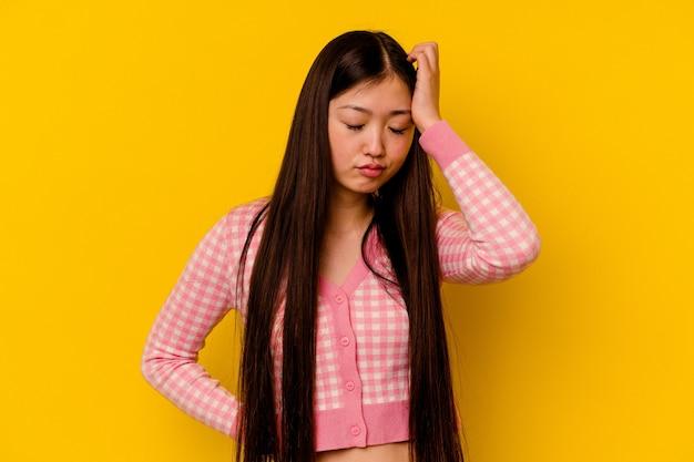 黄色の壁に孤立した若い中国人女性は疲れていて、頭に手を置いて非常に眠い