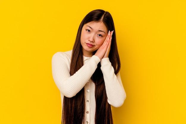 手で口を覆う疲れたジェスチャーを示すあくびをする黄色の壁に孤立した若い中国人女性