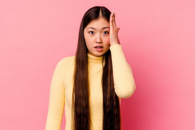 Young chinese woman isolated on pink background being shocked, she has remembered important meeting.