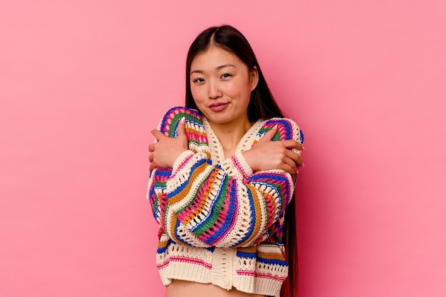 Young chinese woman isolated on pink background hugs, smiling carefree and happy.