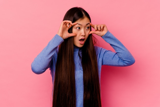 Young chinese woman isolated on pink background keeping eyes opened to find a success opportunity.