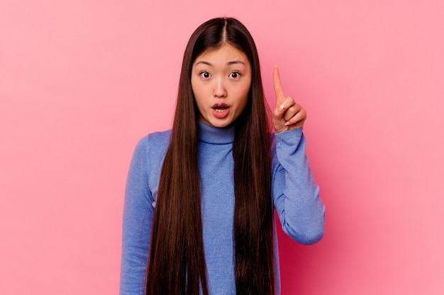 Young chinese woman isolated on pink background pointing upside with opened mouth.