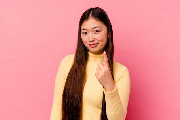 Young chinese woman isolated on pink background pointing with finger at you as if inviting come closer.