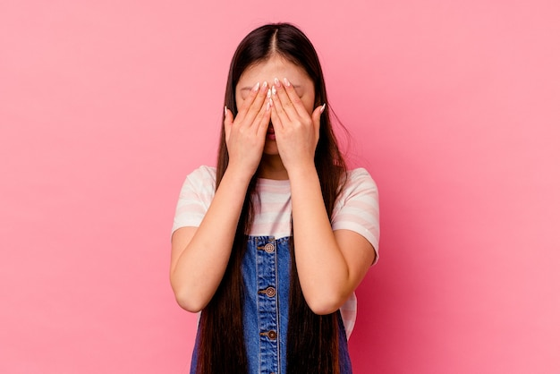 Young chinese woman isolated on pink wall afraid covering eyes with hands.