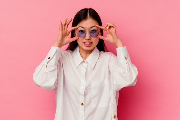 Young chinese woman isolated on pink wall keeping eyes opened to find a success opportunity