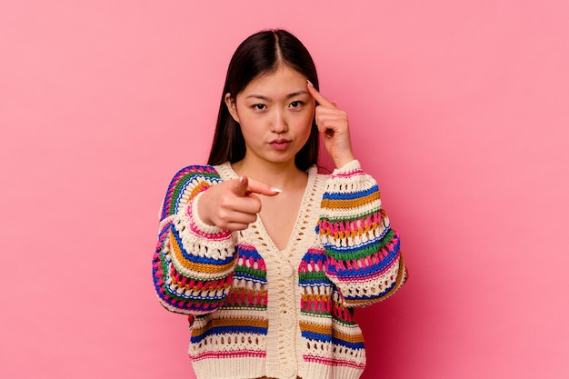 Young chinese woman isolated on pink wall pointing temple with finger, thinking, focused on a task