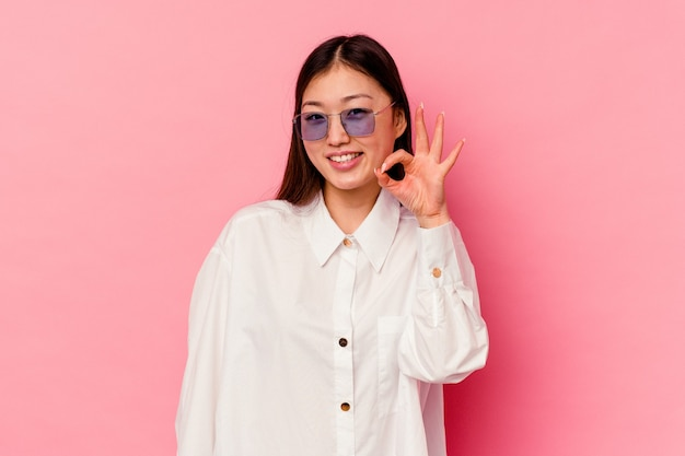 Young chinese woman isolated on pink winks an eye and holds an okay gesture with hand.