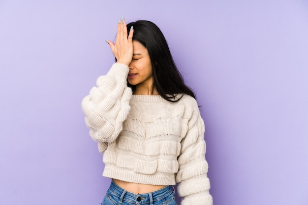 Young chinese  woman isolated on a purple space forgetting something, slapping forehead with palm and closing eyes.