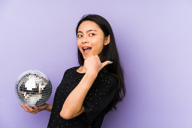 Young chinese woman isolated on a purple wall raising fist after a victory, winner concept.