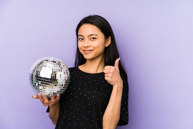 Young chinese woman isolated on a purple wall smiling and pointing aside, showing something at blank space.