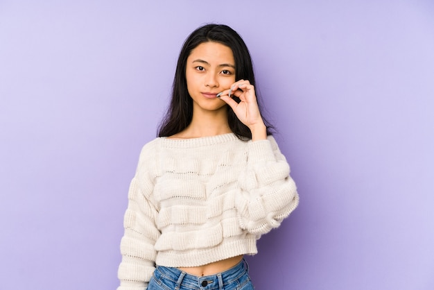 Young chinese  woman isolated on purple with fingers on lips keeping a secret.