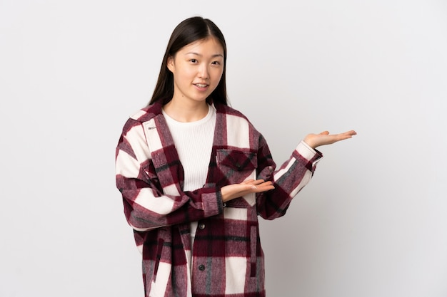 Young chinese woman over isolated white wall extending hands to the side for inviting to come