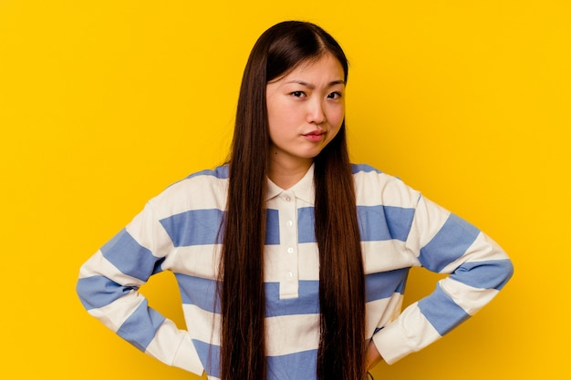 Young chinese woman isolated on yellow background confused, feels doubtful and unsure.