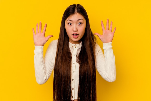 Young chinese woman isolated on yellow background having an idea, inspiration concept.