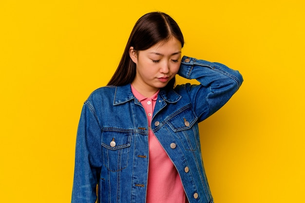 Young chinese woman isolated on yellow background having a neck pain due to stress, massaging and touching it with hand.