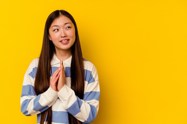 Young chinese woman isolated on yellow background making up plan in mind, setting up an idea.
