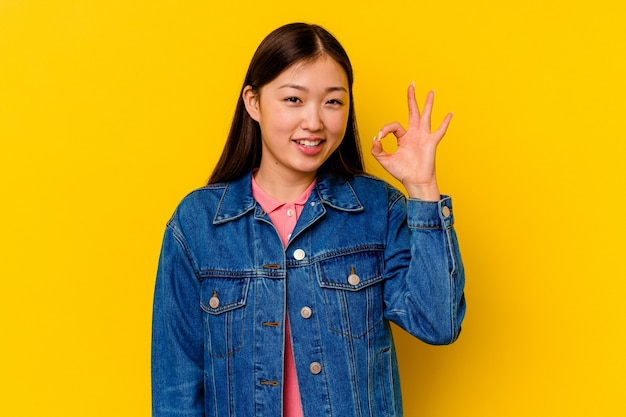 Young chinese woman isolated on yellow background winks an eye and holds an okay gesture with hand.
