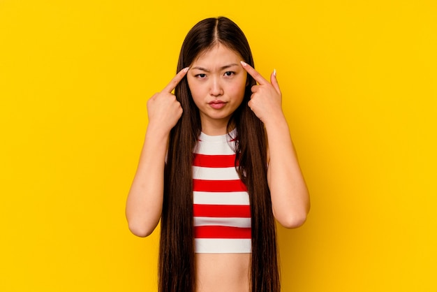 Young chinese woman isolated on yellow focused on a task, keeping forefingers pointing head.