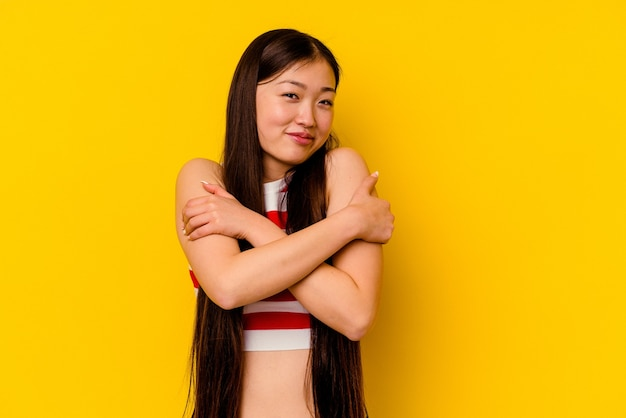 Young chinese woman isolated on yellow hugs, smiling carefree and happy.