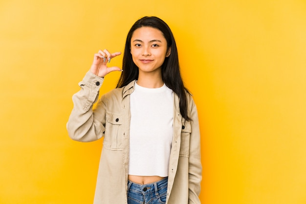 Young chinese woman isolated on a yellow wall holding something little with forefingers, smiling and confident.