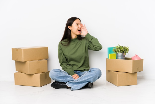 Young chinese woman moving to a new home shouting and holding palm near opened mouth.
