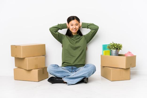 Молодая китаянка переезжает в новый дом, прикрывая уши руками, пытаясь не слышать слишком громкий звук.