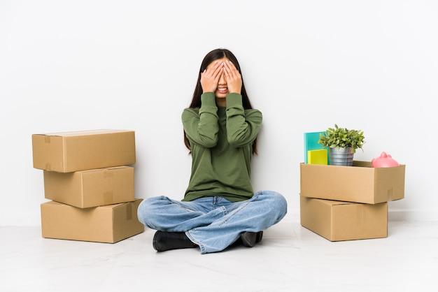 Молодая китаянка, переезжающая в новый дом, прикрывает глаза руками, широко улыбаясь, ожидая сюрприза.