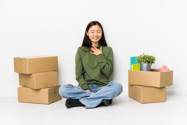 新しい家に引っ越してきた若い中国人女性は、胸に手を当てて大声で笑います。