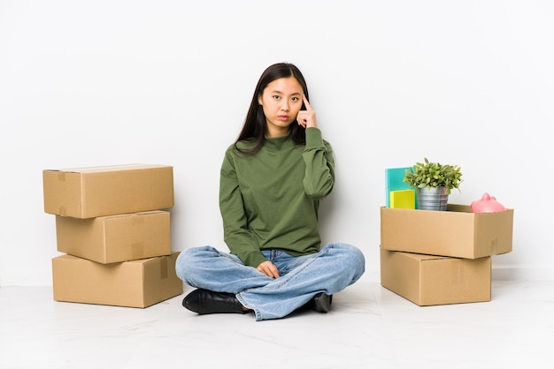 Молодая китаянка переезжает в новый дом, указывая пальцем на храм, думая, сосредоточившись на задаче.