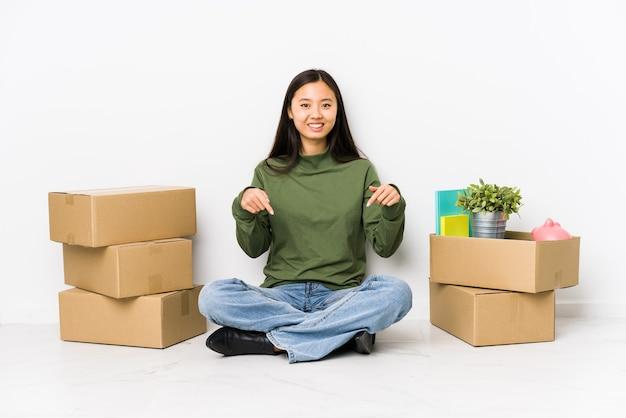 新しい家に移動する若い中国人女性は、指で下向き、前向きな気持ちです。