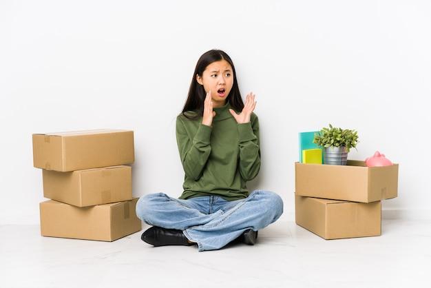 新しい家に移動する若い中国人女性は大声で叫び、目を開いたままにし、手を緊張させます