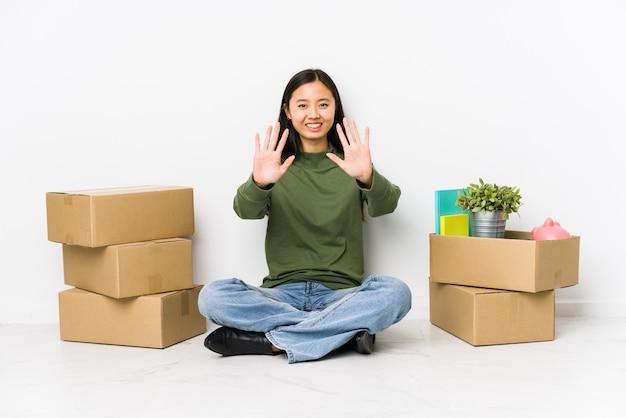 Молодая китайская женщина двигая к новому дому показывая номер 10 с руками.