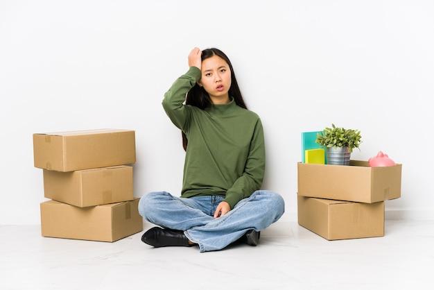 新しい家に引っ越している若い中国人女性は、頭を抱えて疲れていてとても眠いです。