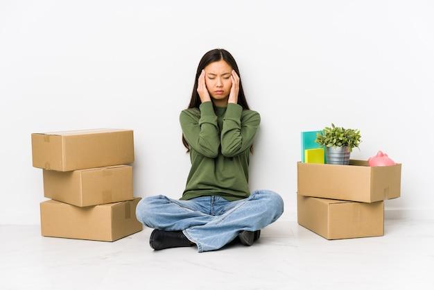 Молодая китаянка, переезжающая в новый дом, трогает виски и страдает головной болью.