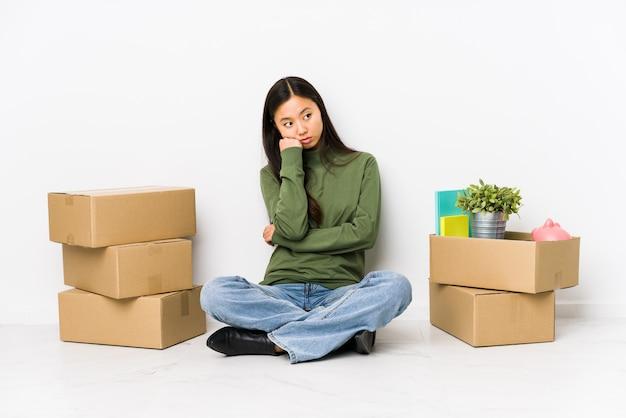 悲しいと物思いにふける、コピースペースを見て新しい家に移動する若い中国人女性。