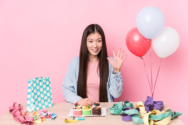 Young chinese woman organizing a birthday isolated smiling cheerful showing number five with fingers.