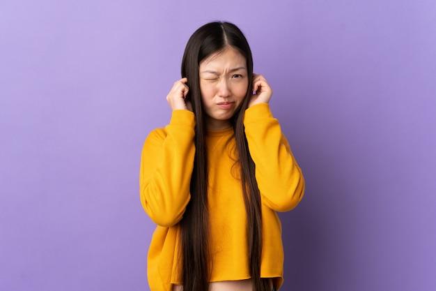 Молодая китайская женщина над изолированной фиолетовой стеной расстроенная и покрывая уши