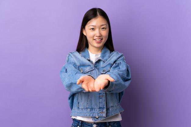 広告を挿入する手のひらに架空のcopyspaceを保持している孤立した紫の壁を越えて若い中国人女性