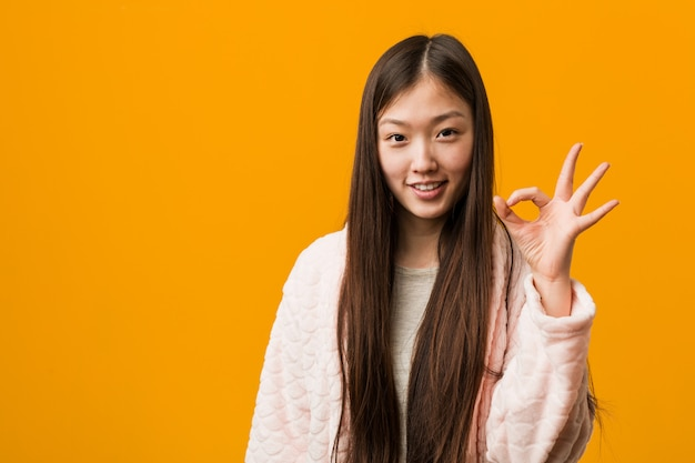 Young chinese woman in pajama cheerful and confident showing ok gesture.