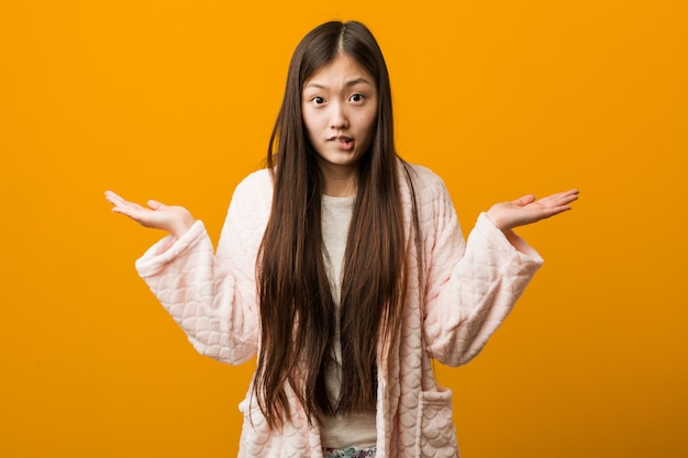Young chinese woman in pajama confused and doubtful raising him hands to hold a copy space.