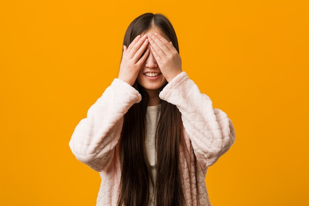 Young chinese woman in pajama covers eyes with hands, smiles broadly waiting for a surprise.
