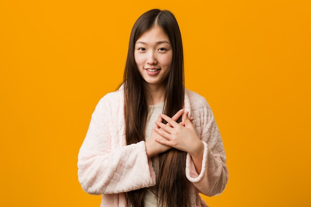 Young chinese woman in pajama has friendly expression, pressing palm to chest. love .