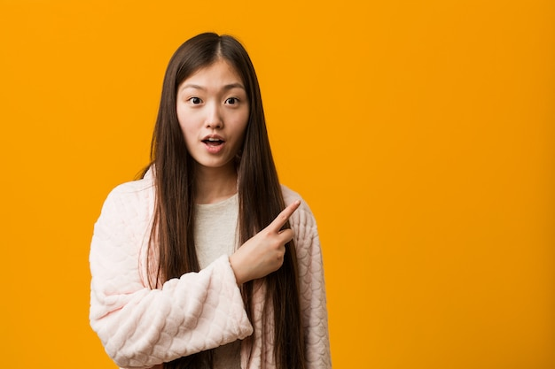 Young chinese woman in pajama pointing to the side